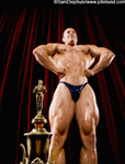 Picture of a body builder flexing his muscles on a stage next to his huge trophy. The mans fists are on his waist and his chest is being accentuated for his pose. Behind the man are tall red velvet theater curtains.